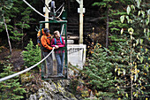 Backpacking couple use a hand tram to cross Winner Creek in the Chugach National Forest of Southcentral Alaska
