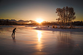 An ice skater skates on Westchester Lagoon at sunsrise in midtown Anchorage, Southcentral Alaska, winter