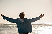 Happy young man with arm outstretched on beach