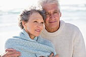 Elderly man embracing his wife from behind on the beach