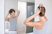 Young beautiful woman adjusting her hair in a bathroom