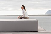 Happy mature woman sitting on ottoman at lakeshore