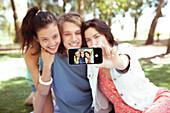 Friends taking selfie together at park