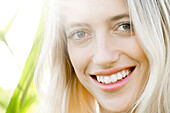 Young woman smiling cheerfully outdoors, portrait