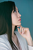 Woman daydreaming with hand under chin