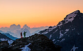 Two hikers at sunrise on the top of Forbici peak in Valmalenco. Valtellina - Lombardy.