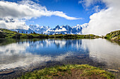 Low clouds and mist around Grandes Jorasses and Mount Blanc while hikers proceed on Lac De Cheserys Haute Savoie France Europe