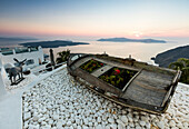 A wooden boat on the white stones overlooking the blue Aegean Sea before dusk at Firostefani Santorini Cyclades Greece Europe