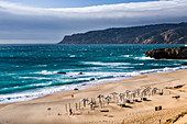 Ocean waves crashing on the sandy beach and bathhouse of Cascais surrounded by cliffs Estoril Coast Lisbon Portugal Europe
