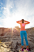 Woman standing in canyon stretching arms