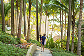 Caucasian mother carry son on path  with palm trees