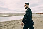 Caucasian groom walking on beach