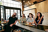 Smiling bartender and customers watching television in bar