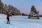 Women skiing in a winter forest, cross-country skiing with full moon, winter landscape, Harz, MR, Sankt Andreasberg, Lower Saxony, Germany