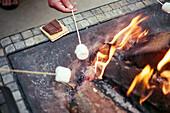 Marshmallows roast over a backyard fire pit