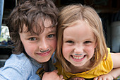 Young siblings wearing fake mustaches, portrait