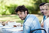 Man enjoying meal outdoors with friends