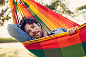Man relaxing in hammock, portrait