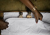 Benin, West Africa, Bopa, miss hounyoga putting the carved wooden figures made to house the soul of her dead twins in a bed.