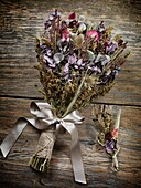 Rustic country wedding bouquet and boutonniere made of dried wild field flowers, artistic still life.