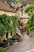 Europe, France, Quercy, Lot, 46, St Cirq Lapopie, tourists amongst the quaint old stone houses lining the streets.