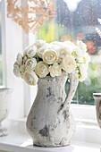 Imitation white roses in jug at window. England UK.