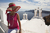 Woman in front of a bell tower in Oia town looking at Caldera, Santorini, Cyclades Islands, Greek Islands, Greece, Europe.