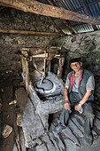 Grinding corn in a small comunially owned water mill in the village of Theth in Northern Albania.
