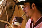 Argentina, Buenos Aires Province, Estancia San Isidro del Llano, gaucho drinking Mate beverage (local herbal tea)