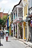 Frau mit Sonnenschirm auf Straße in der Altstadt von  Phuket Town, Phuket, Thailand