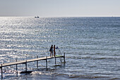 Two persons on a footbridge at the baltic sea, Rødvig, Stevns Peninsula, Island of Zealand, Scandinavia, Denmark, Northern Europe