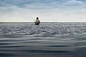 An angler standing in the water of the Bodden in Dierhagen. Dierhagen, Darß, Mecklenburg-Vorpommern, Germany