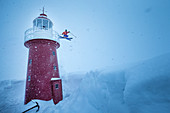 Young male skier jumping at a lighthouse in the deep snow, Andermatt, Uri, Switzerland