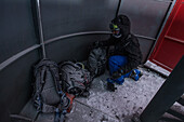 Young man get snow-covered bags out of a ski lift, Andermatt, Uri, Switzerland