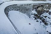 Young male skier riding down a hill next to a stone bridge, Andermatt, Uri, Switzerland