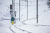 Young male skier walking at a snow-covered railroad track, Andermatt, Uri, Switzerland