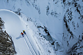 Two young freeskier hiking through the deep powder snow in the mountains, Andermatt, Uri, Switzerland
