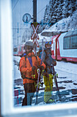 Two young male skier standing at a railroad crossing, Andermatt, Uri, Switzerland