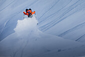 Young male skier doing a backflip over a cliff apart the slopes, Andermatt, Uri, Switzerland
