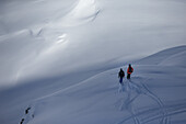 Two young skiers planing their next line in the deep powder snwo apart the slopes, Andermatt, Uri, Switzerland