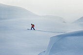 Young male skier whiking through the deep powder snow apart the slopes, Andermatt, Uri, Switzerland