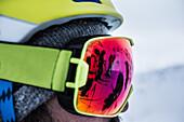 Reflexion of three young male skiers in ski goggles, Andermatt, Uri, Switzerland