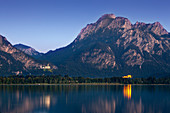 View over lake Forggensee to Neuschwanstein castle, Hohenschwangau castle and Saeuling, Allgaeu Alps, Allgaeu, Bavaria, Germany