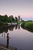 Angler at the twin windmills, at full moon, Greetsiel, East Friesland, Lower Saxony, Germany