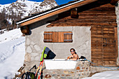 Italy, Valle d'Aosta (The Aosta Valley), touring skier having a break in an altitude chalet under the top of Gran Pays Mountain