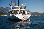 Two young women jump from deck platform of motor sailing cruise ship M/S Panorama (Variety Cruises) during swim stop, near Korcula, Dubrovnik-Neretva, Croatia