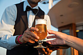 Glass of cold beer is served by bar steward aboard motor sailing cruise ship M/S Panorama (Variety Cruises), Adriatic Sea, near Albania