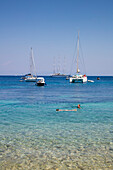 People swim in clear waters along pristine bay with sailboats and motor sailing cruise ship M/S Panorama (Variety Cruises) at anchor in distance, Paxos, Ionian Islands, Greece