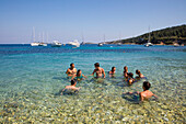 Group of people relax in water near beach, Paxos, Ionian Islands, Greece