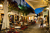 People enjoy drinks at outdoor seating of bar and cafe at night, Gaios, Paxos, Ionian Islands, Greece